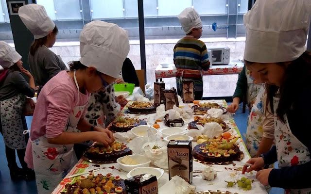 Niños participando en el taller de cocina creativa organizado en la biblioteca municipal de Illescas