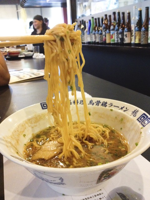 Ramen noodles being held by chopsticks