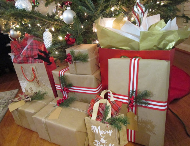 Wrapped Christmas gifts with tree sprigs, striped ribbon, berries, twine and brown paper