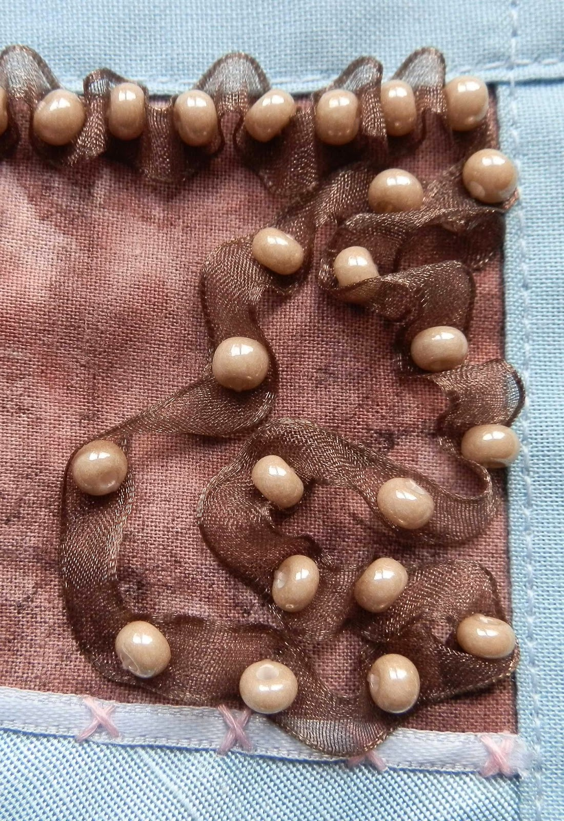 small beige beads with brown ribbon on brown fabric