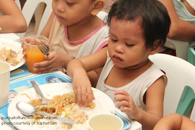 December 2012 Outreach Program. A toddler who is eating noodles using his hand.