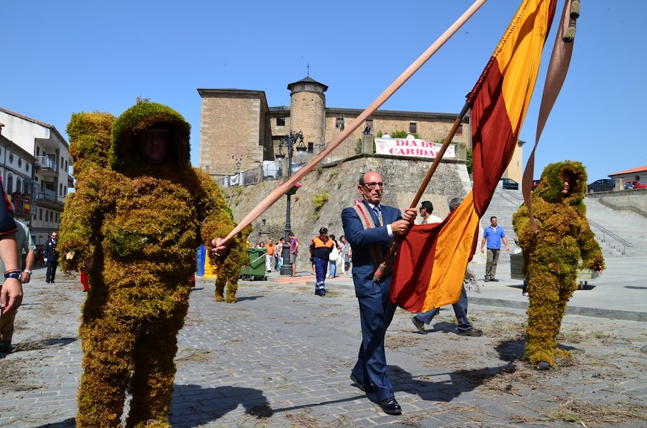 procesion del corpus ccon un concejal portando la bandera de españa entre dos hombres de musgo