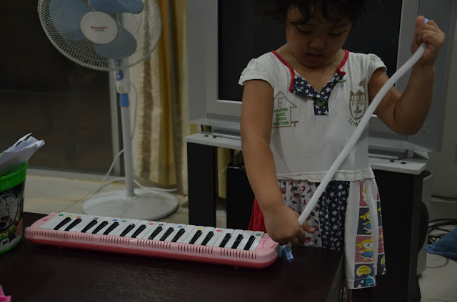 Kecil playing the pianika indoor