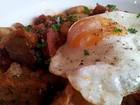 Panfried chorizo, white beans and crispy pork belly with spanish onion and fried egg