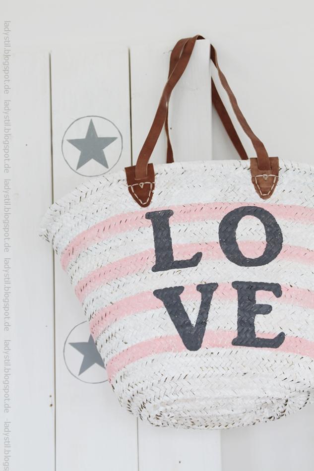 weiße rosa gestreifte Korbtasche mit großem anthrazitfarbenem Love Schriftzug an einer weißen Tafel mit grauen Sternen für den Bloggeroptimierungsfotowettbewerbbeipixum
