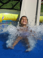 Image of Child going down water slide in Kids Wetsuits