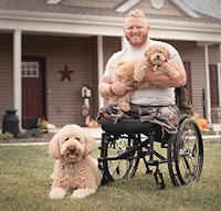 Wounded vet in wheelchair in front of his house.