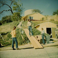 Gary's house (on the hill) and the guys getting ready to move a piano up to it
