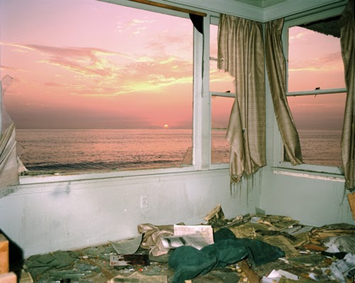 Zuma Series (1977) by John Divola, post-hurricane sunset through battered windows, beautiful abandoned house, torn gold curtains