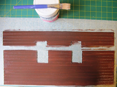 Two freshly-painted pieces of dolls' house miniature weatherboarding, with window holes cut out.