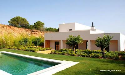 Fondo con jardín y piscina de una de las casas del complejo