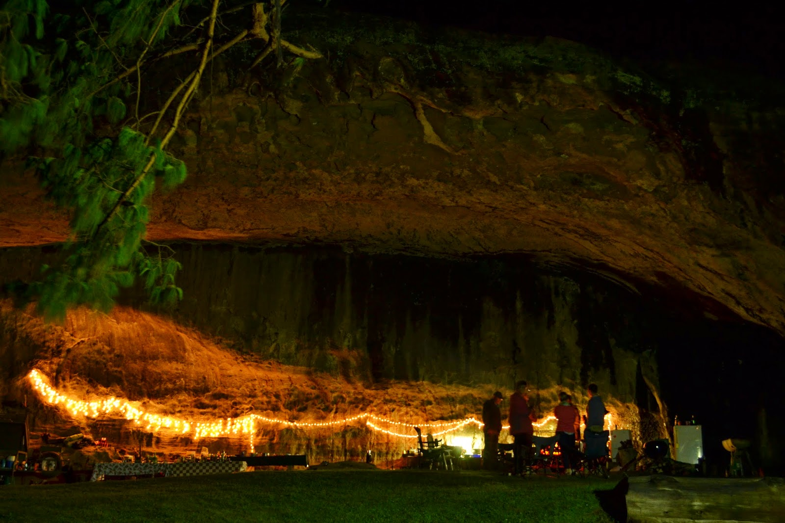 Night picture of people camping in big cave with Christmas Lights