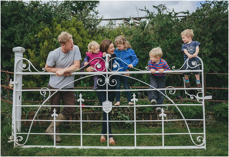 A family leaning on a farm gate