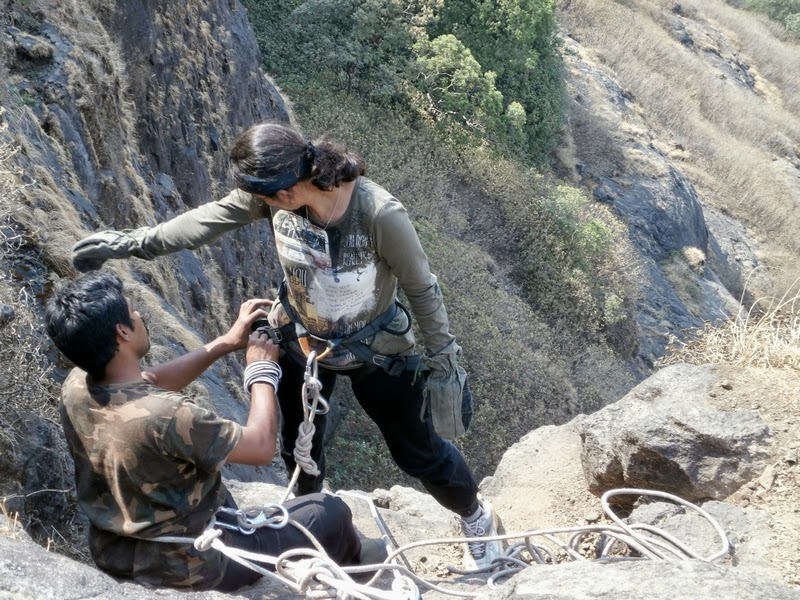 Nilesh fastening the harness of Rashmi before she rappelled down the 40 feet rock patch on Madan