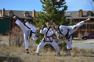 Black belt mom does a kick with her two taekwondo kids
