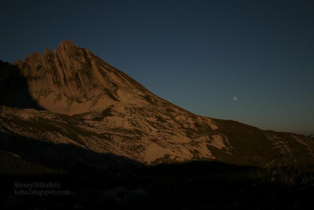 Скала в оранжевом свете заката, на фоне луны