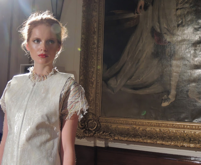 Model in white stands in front of decadent painting at the Freemasons' Hall, London
