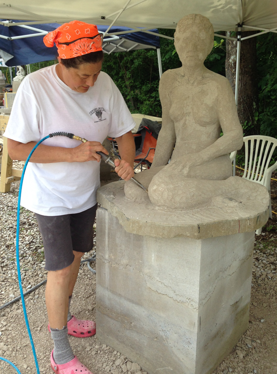 Amy Brier uses an air chisel to sculpt a figure out of Indiana limestone.