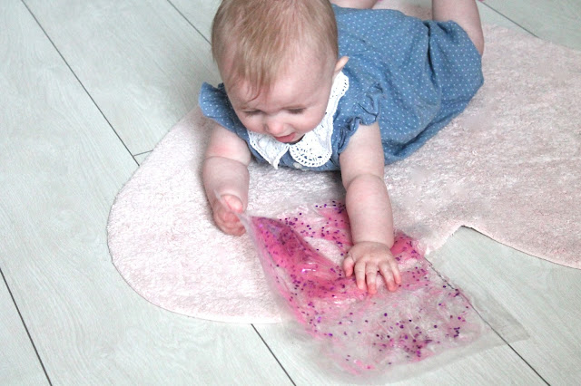 baby lying on white wooden floor playing with pink glitter diy sensory mat