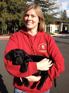 Gina smiles holding a young black Lab puppy.