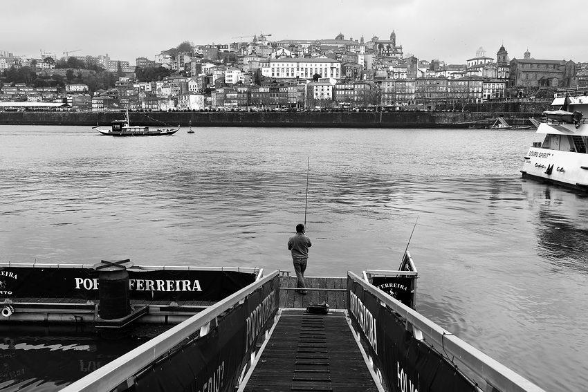 Foto a preto e branco no Cais de Gaia com um passadiço em primeiro plano e nele um homem a pescar. No rio um barco rabelo em circuito turístico e ao fundo a zona da Ribeira - Porto
