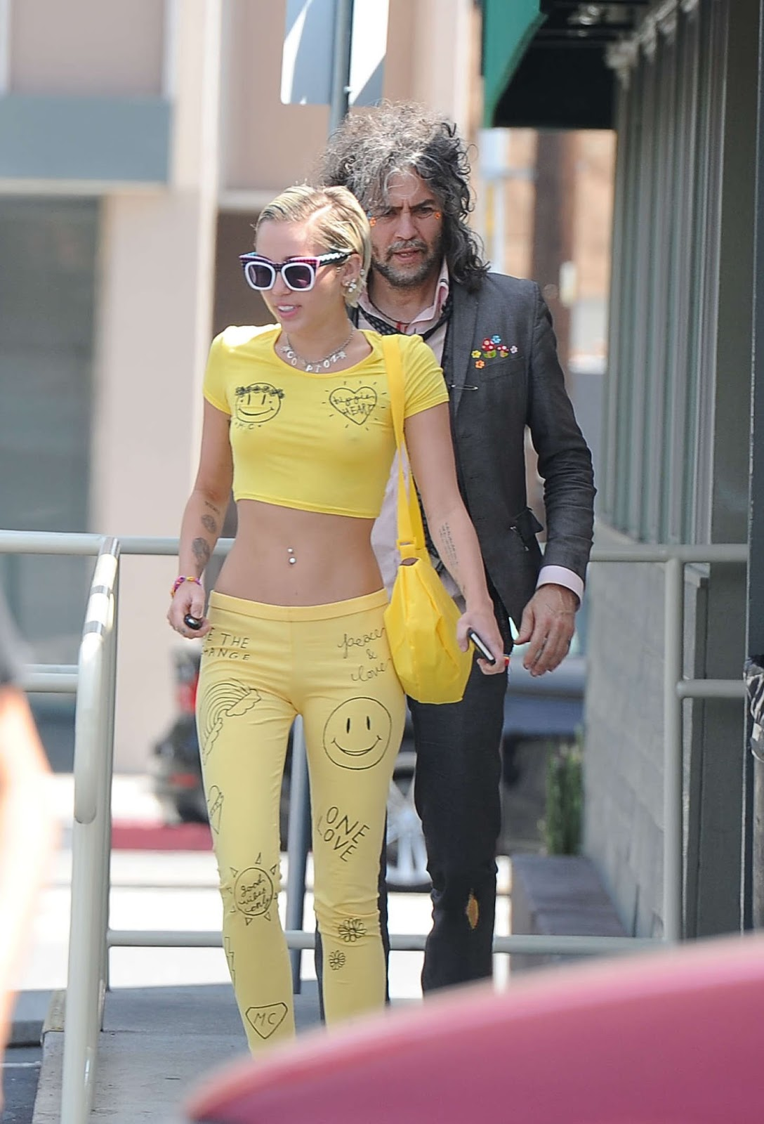 Miley Cyrus goes braless in a yellow cropped top and matching trousers