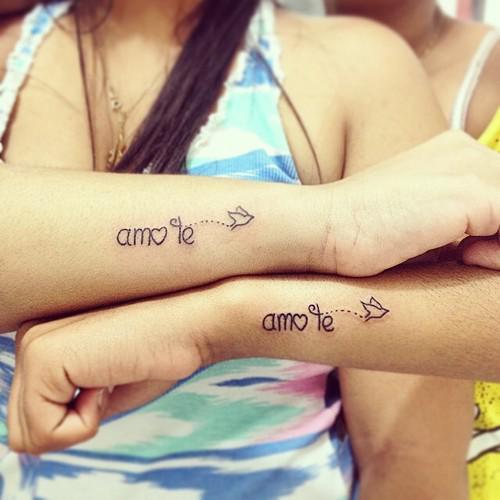 dos chicas con tatuajes de frases en sus antebrazos que dicen te amo