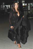 Kim Kardashian shows off her curves in a black shirt