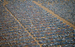 Stockpiles of unsold vehicles provide a testament to overproduction fueled by avarice