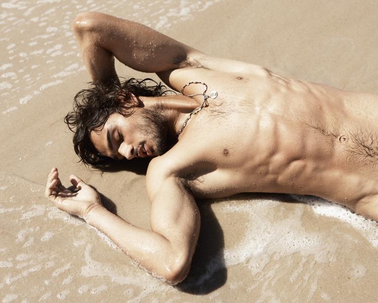 Marlon Teixeira faz pose sensual deitado na areia