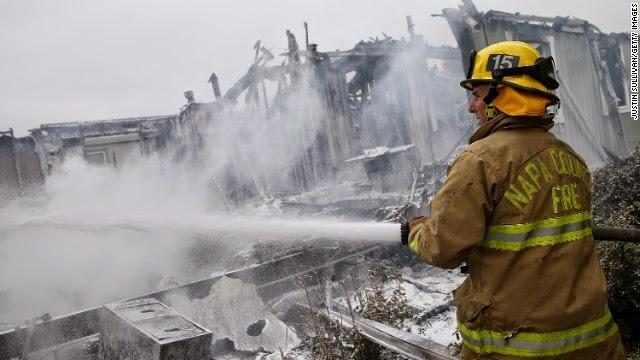Pemadam kebakaran Napa County semprotan busa pada hot spot dari kebakaran di sebuah taman rumah mobile di Napa, California, mengikuti sebuah besarnya 6.0 skala righter gempa pada tanggal 24 Agustus.