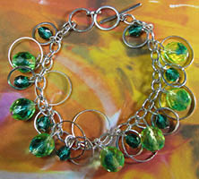 Pretty bracelet has dramatic green beads encircled in silver rings hanging from single chain