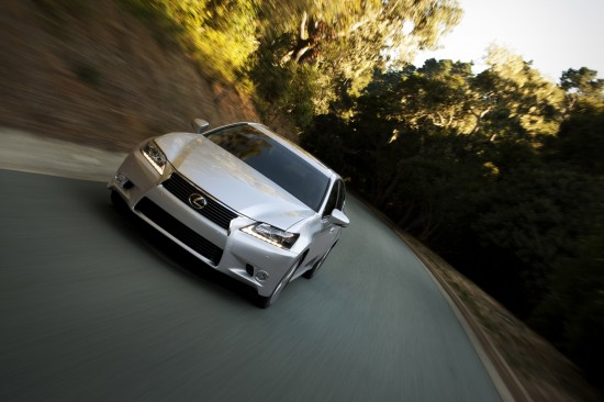 Front view, tilted, of 2012 Lexus GS350 driving toward the camera on two lane winding road