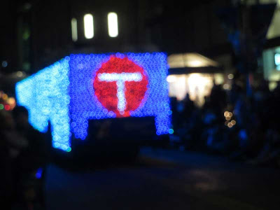 Blurry photo of a bus wrapped in blue Christmas lights with a red circle on the back with a white T in it