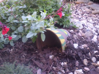 brightly painted sideways half buried flower pot for frog house