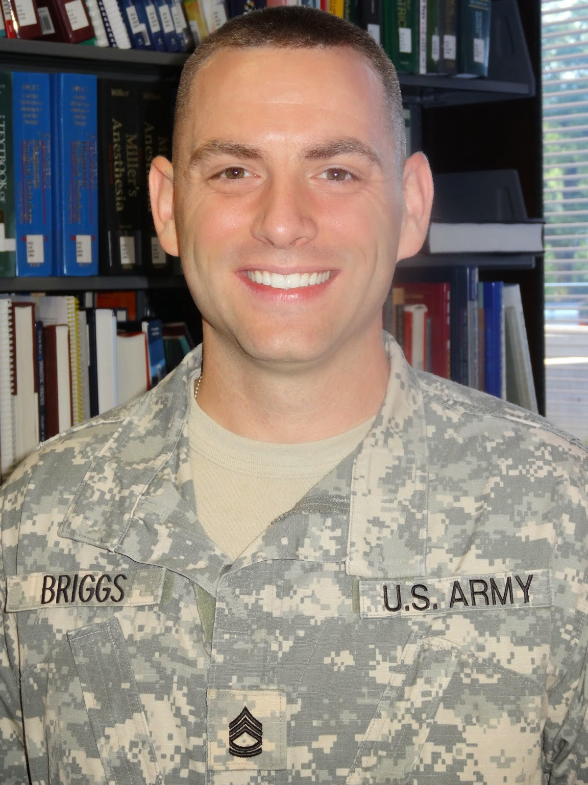 Jerald Briggs in United States Army attire posing for a photo in a library.