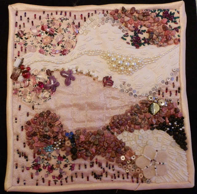 Embroidery piece made of patchwork of pink and cream fabrics with variety of beads sewn on