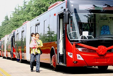 Two passengers in Zhengzhou, China, watch the launch of hybrid buses. (Credit: Yutong Bus) Click to enlarge.