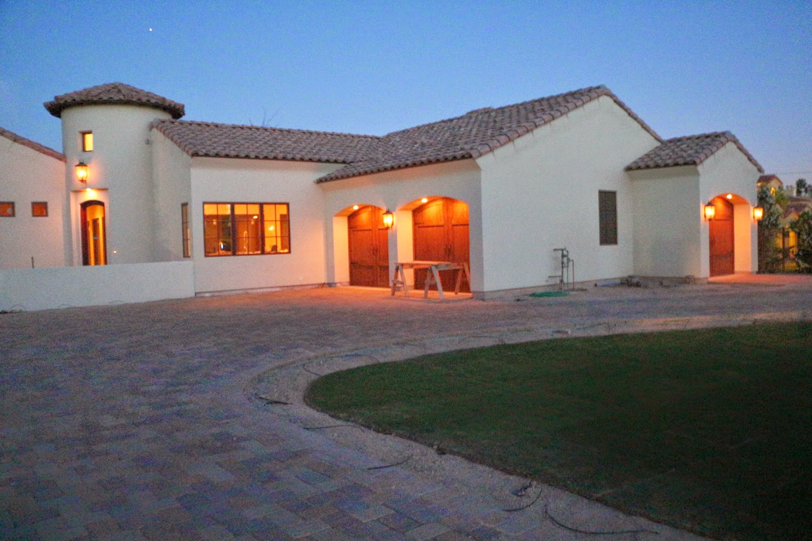 paver driveway, wood garage doors, arched garage door opening, spanish colonial house