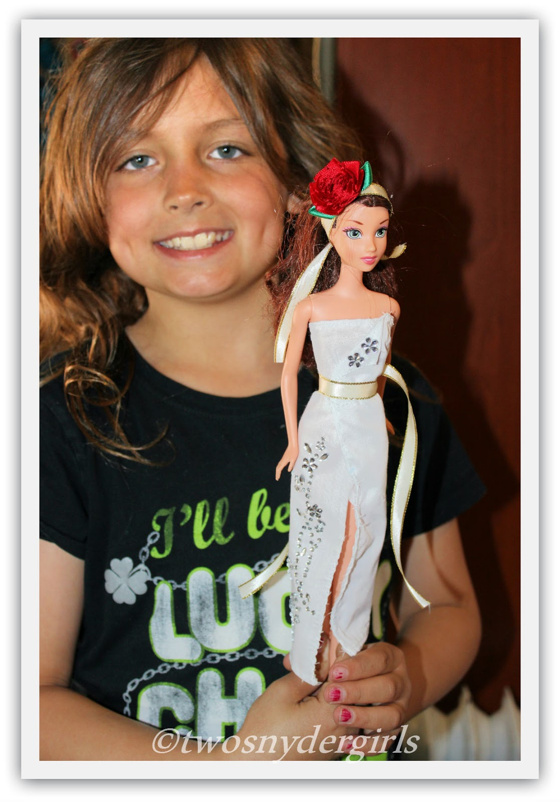 Young girl smiling holding her Barbie Doll clothing design