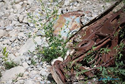 a rusty wreck of a car under a rock slide