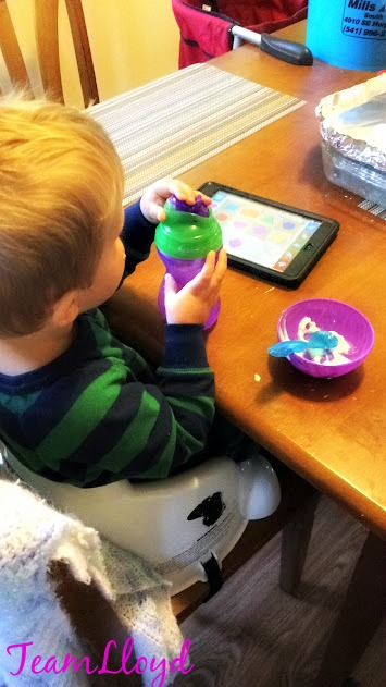 Little boy eating yogurt and playing on iPad