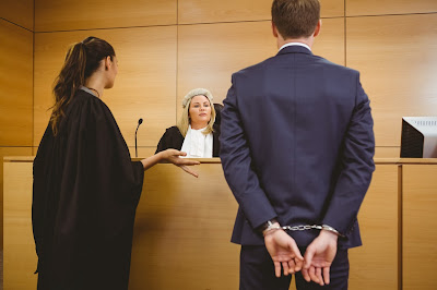 Man in handcuffs appears before a wigged judge
