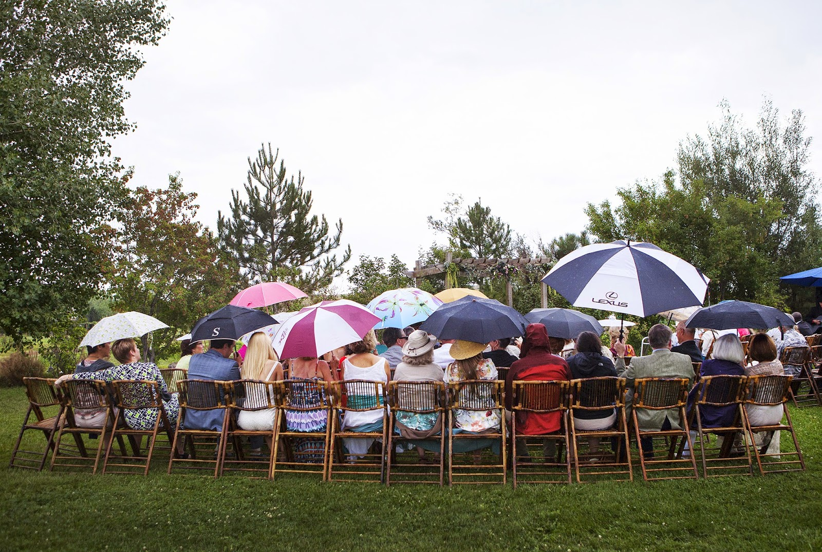 Guests sitting in the rain, waiting on the bride to walk down the aisle