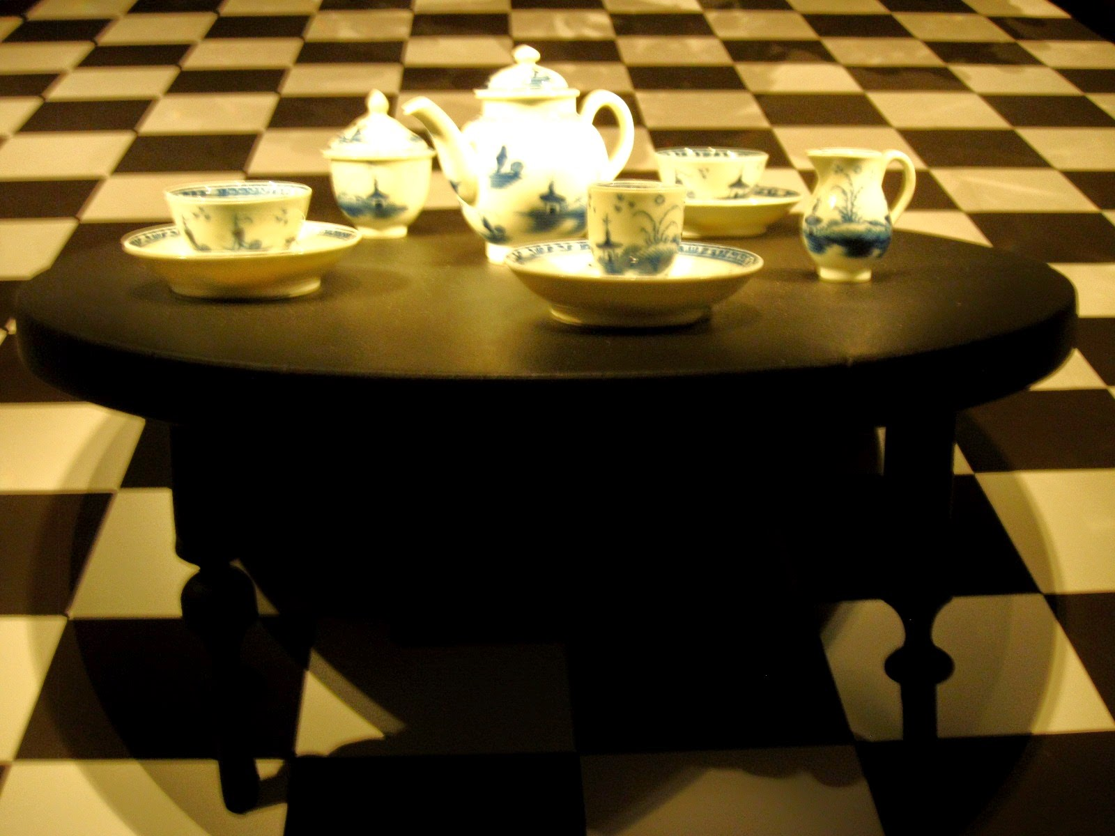 Miniature tea set on display in a museum, on a miniature antique table