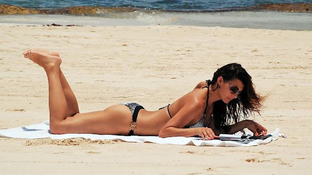 Vrouw leest boekje of tijdschrift op het strand