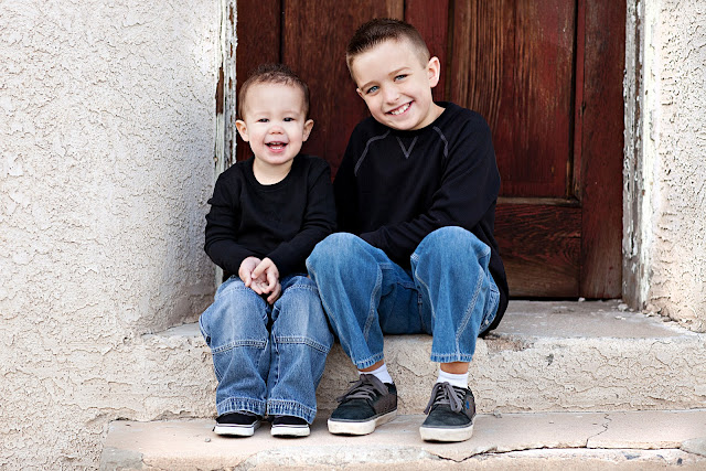 Tucson brothers smile at child photographer sitting on cement steps