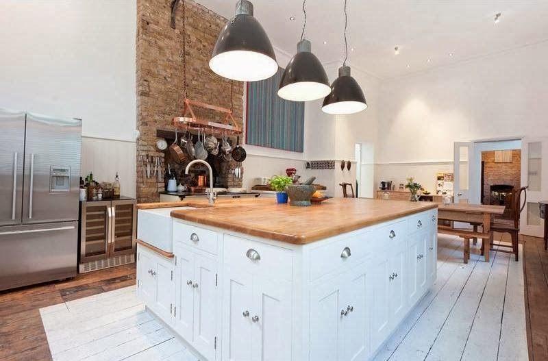 Kitchen in London flat with black pendant lights and brick fireplace