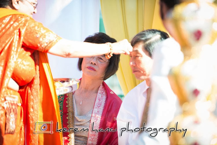 Priestess is placing kumkum on the bride's parents forehead