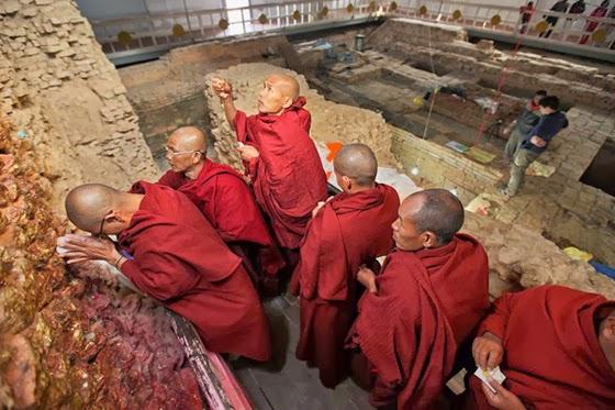 Monaci in pellegrinaggio al tempio di Lumbini. Sullo sfondo gli scavi archeologici che interessano l'area Fotografia di Ira Block, National Geographic